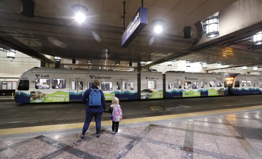 FILE - In this Nov. 6, 2019, file photo, southbound passengers wait as they look across at a northbound Sound Transit light rail train at an underground station in downtown Seattle. The Washington Supreme Court on Thursday, Feb. 13, 2020, upheld vehicle registration tax increases in the Puget Sound area, a decision that preserves billions of dollars in voter-approved money earmarked for light trail and other projects.