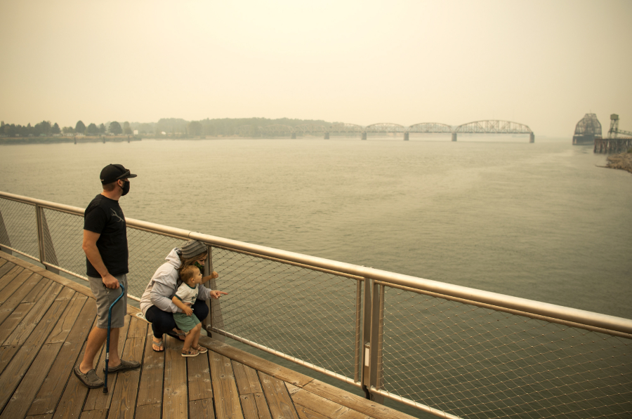 Brent McCarthy, left, and Marissa Matthews, right, play on the Vancouver Waterfront pier with their son Xavier, 2, on Sept. 10, 2020. The family evacuated from their home just outside of Salem, Ore., two days earlier to escape the smoke and fire risk. Longer and hotter fire seasons increase the likelihood of smoke finding its way to Vancouver.