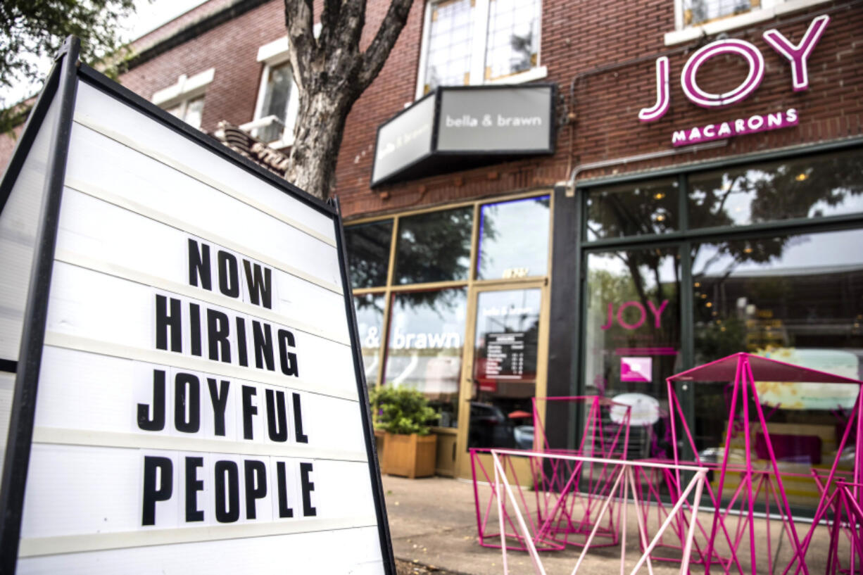 """A """"Now Hiring"""" sign stood outside JOY Macarons in Dallas earlier this summer. (Lynda M."""