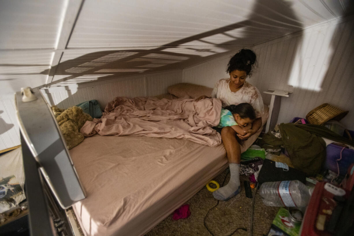 Camp fire victim and volunteer firefighter Inez Salinas holds her 5-year-old daughter River at bedtime inside their tiny home on July 22, 2021 in Concow, California.