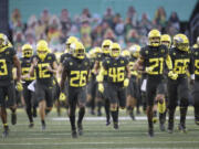 Oregon players take the field at an empty Autzen Stadium for an NCAA college football game Saturday, Nov. 7, 2020, in Eugene, Ore.