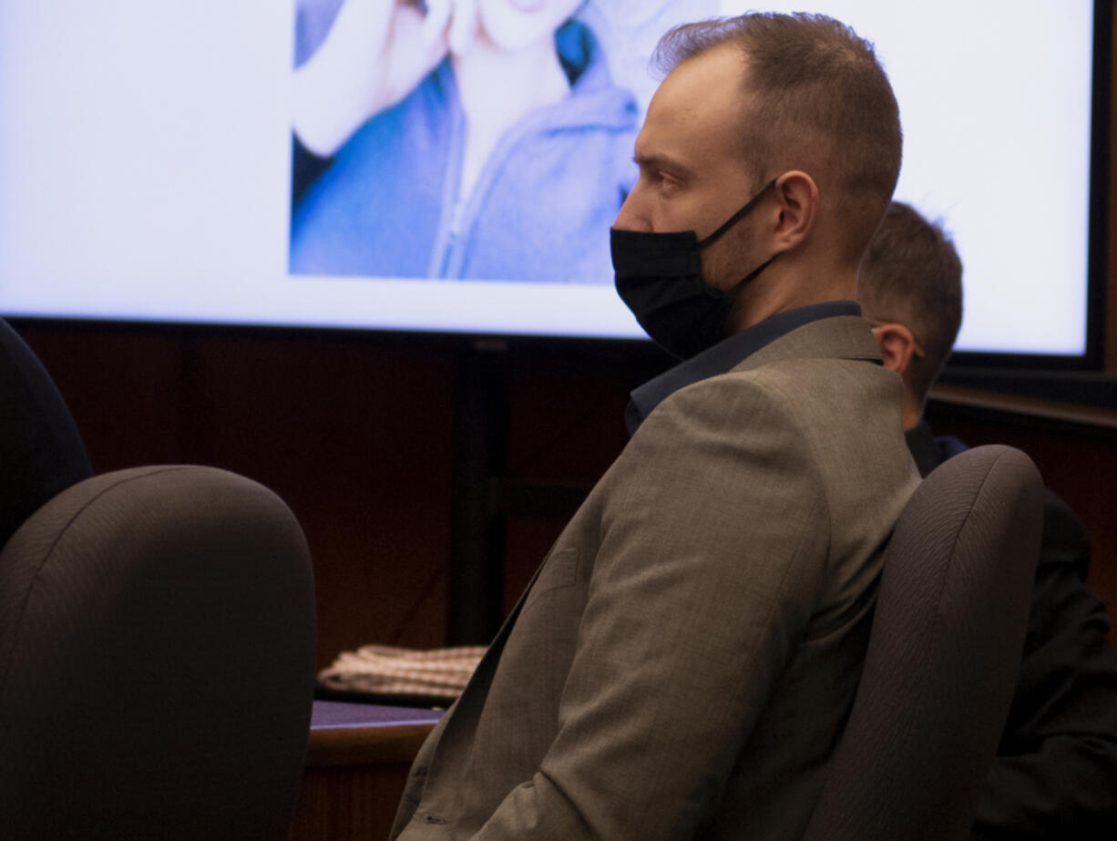 Defendant David Bogdanov listens to the prosecution's opening statement, with a photo of 17-year-old Nikki Kuhnhausen on a projection screen behind him, at his murder trial in Clark County Superior Court.
