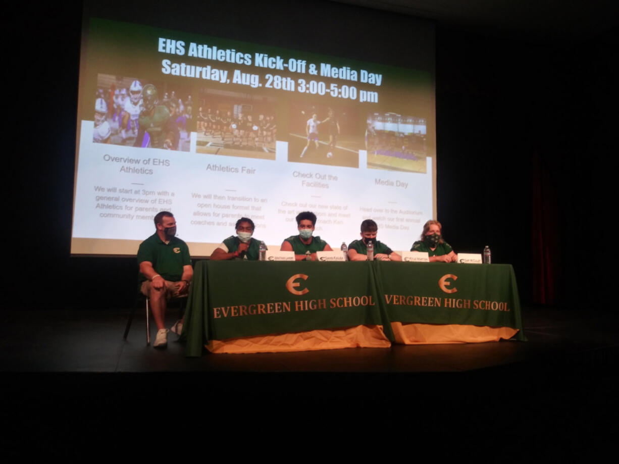 Evergreen High School football coach and athletic director Christian Swain sits with football players (from left) Jonathan Landry, David Kailea, Kyle Norton and Gary McCulley at Evergreen's Athletics Kick-off and Media Day.