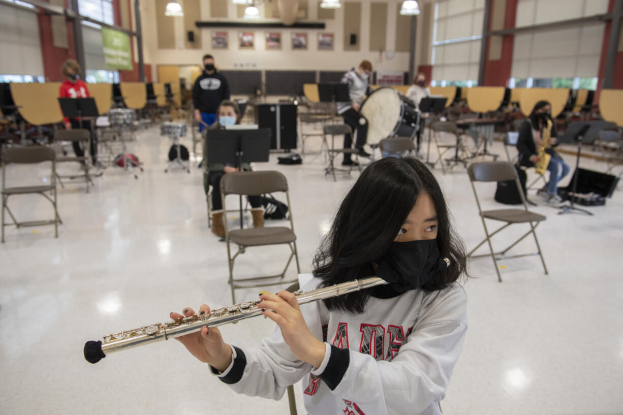 Valyssa Nguyen wears a specialized band mask and a cover on the end of her flute for COVID-19 protections during band class back in the spring at Laurin Middle School. Most of Clark County's school districts begin the 2021-22 school year next week, and mask wearing is required for all employees and students inside school buildings. That also includes specialized masks for performing arts classes and activities.