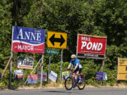 A cyclist passes signs for the upcoming election along Northwest Lakeshore Avenue on the afternoon of July 22.