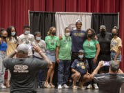 Tobias Merriweather, an incoming senior at Union High School, in navy blue, joins loved ones on stage at Union High School after announcing he will play college football at Notre Dame on Wednesday afternoon, Aug. 4, 2021.