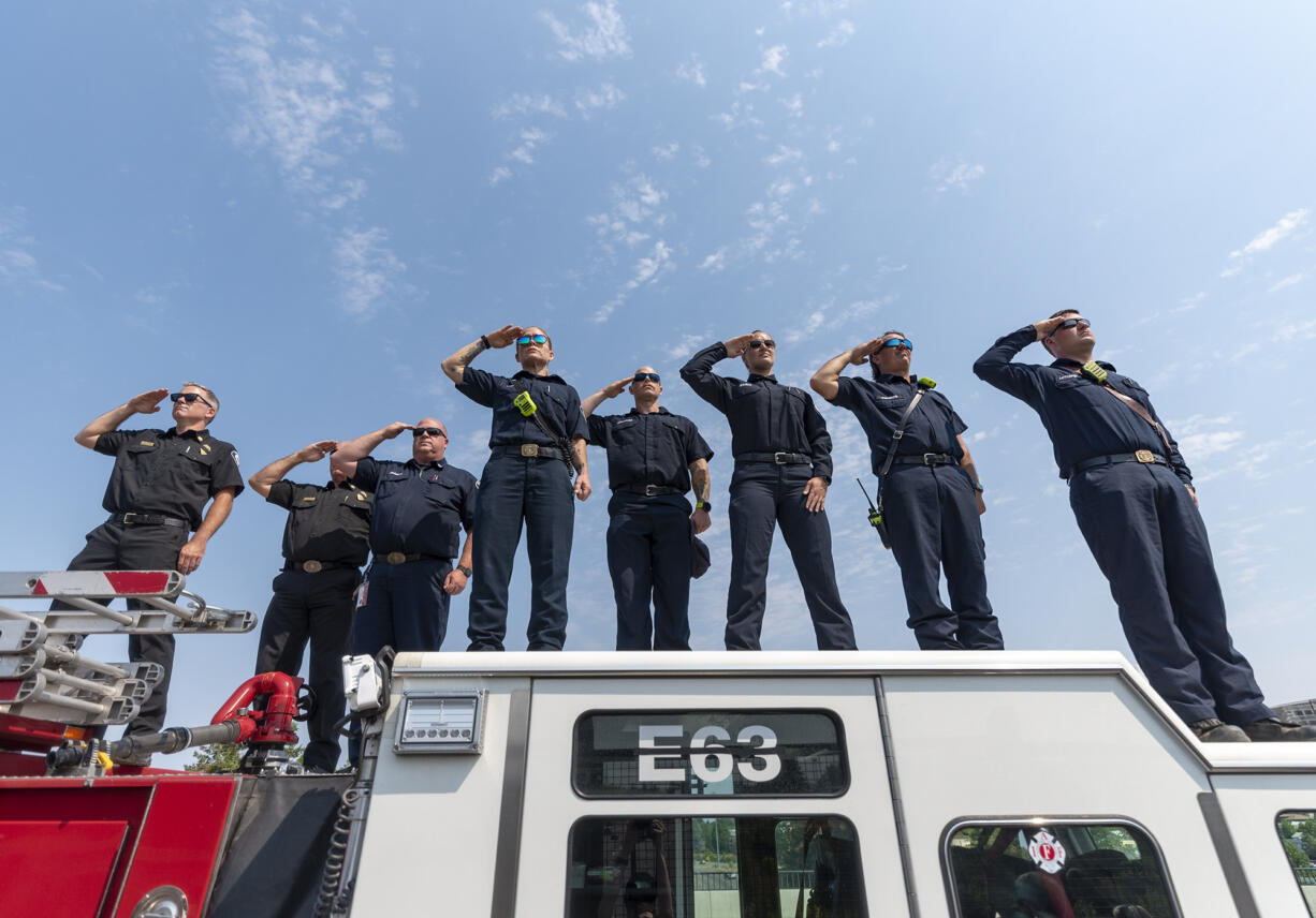 EMT's and firefighters from Clark County Fire District 6 stand atop a firetruck and salute as a funeral procession for Clark County Sheriff's Sgt. Jeremy Brown drives north on I-5 on Tuesday, Aug. 3, 2021, at the NE 139th Street overpass in Vancouver.