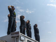 EMTÕs and firefighters from Clark County Fire District 6 stand atop a firetruck and salute as a funeral procession for Clark County Sheriff's Sgt. Jeremy Brown drives north on I-5 on Tuesday, Aug. 3, 2021, at the NE 139th Street overpass in Vancouver.