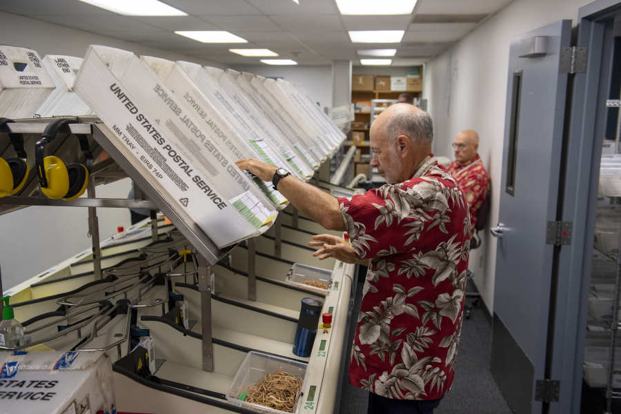 Elections office employee Brian Hopper sorts envelopes containing returned ballots at the elections office on Tuesday morning.