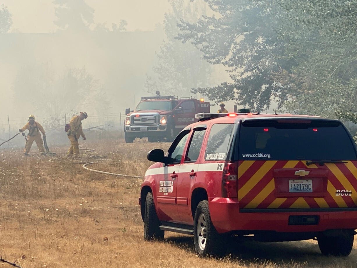 Clark County Fire District 6 crews battle a stubborn brush fire Monday afternoon near Klineline Pond. Pushed by shifting winds and fueled by dry underbrush, the brush fire sent smoke billowing toward Interstate 5.