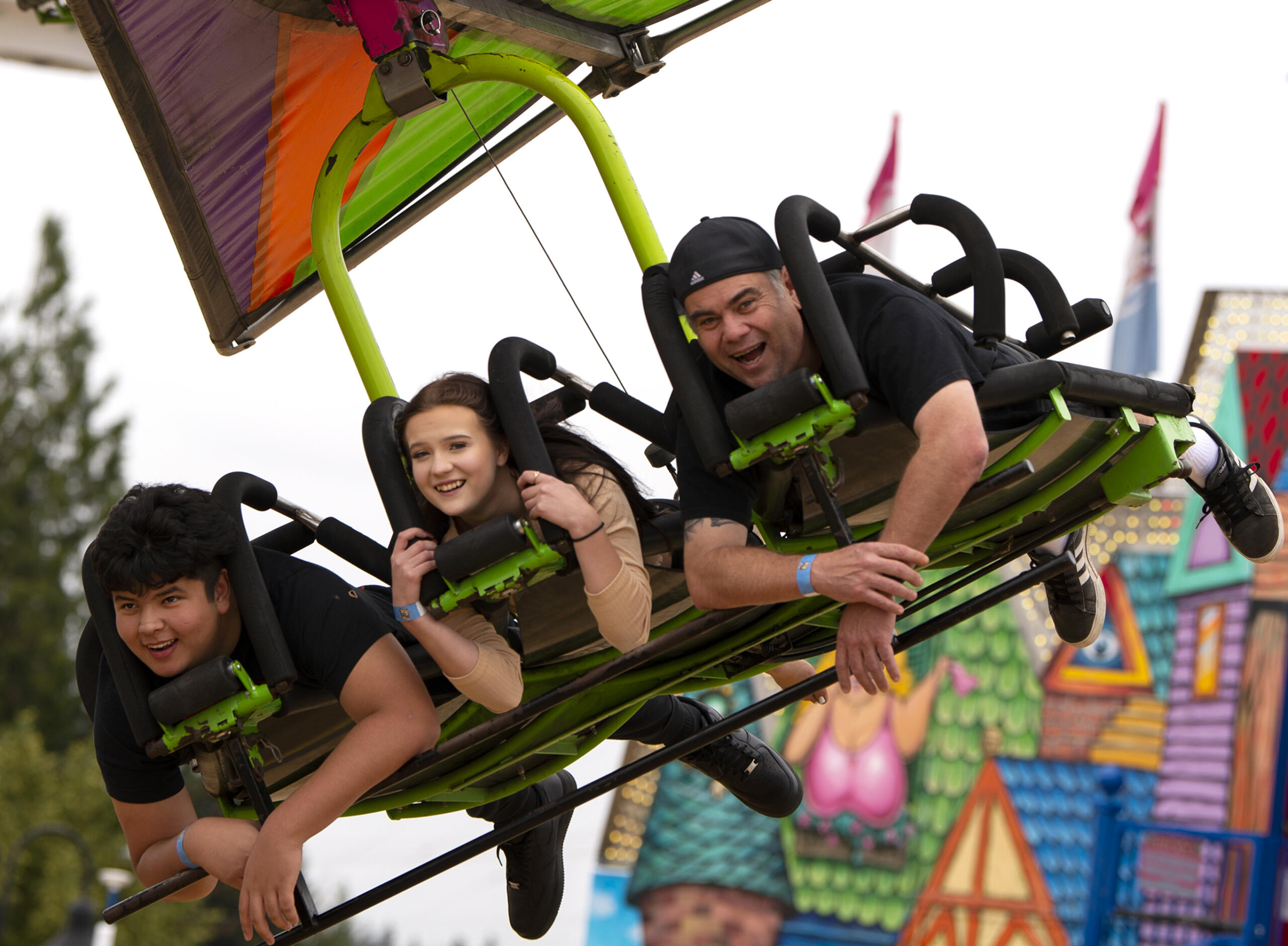 """From left, Jordan Higgins, Kyra Tiaga and Ted Tiaga smileas they ride """"Cliff Hanger"""" during a carnival on Saturday, Aug. 7, 2021, at the Clark County Fairgrounds. While the fair was canceled this year, Clark County Event Center is hosting several events in the Family Fun Series, including a carnival which runs through Aug. 15 and is open until 11 p.m. each night."""