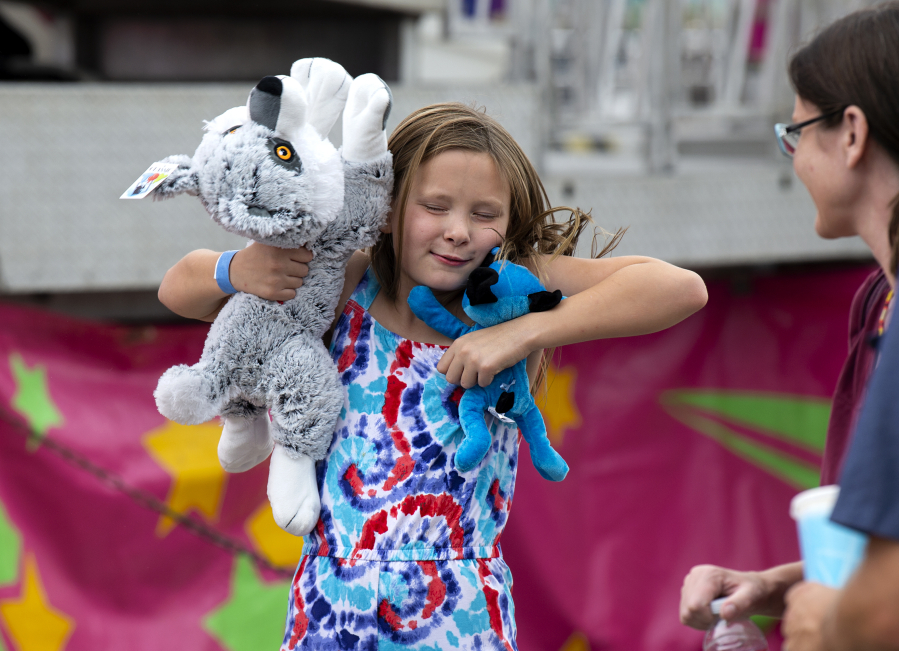 Alivia Pietrzykowski, 8, jumps for joy after winning a giant stuffed dog during a carnival on Saturday at the Clark County Fairgrounds. The carnival will run through Aug. 15 and is open until 11 p.m. each night.