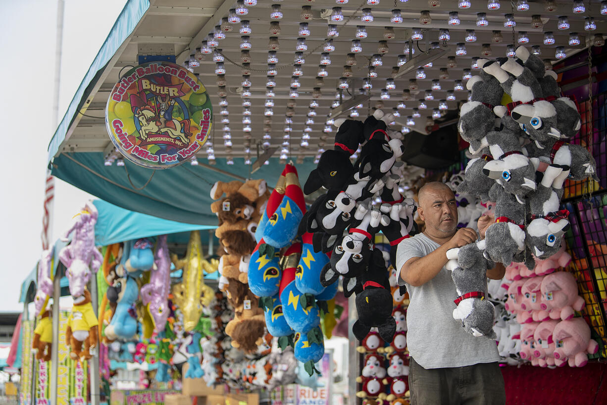 Alejandro Trejo of Butler Amusements sets out some of the prizes at the carnival.