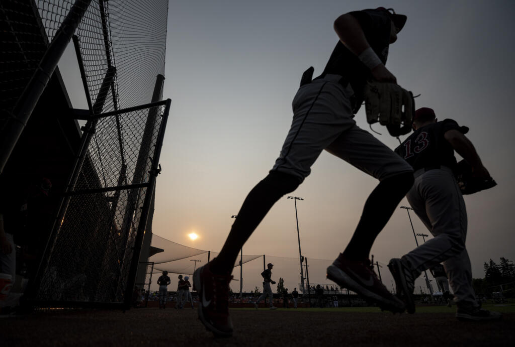 Players take the field under smoky skies Saturday, Aug. 14, 2021, during a playoff game between the Ridgefield Raptors and the Corvallis Knights at the Ridgefield Outdoor Recreation Complex.