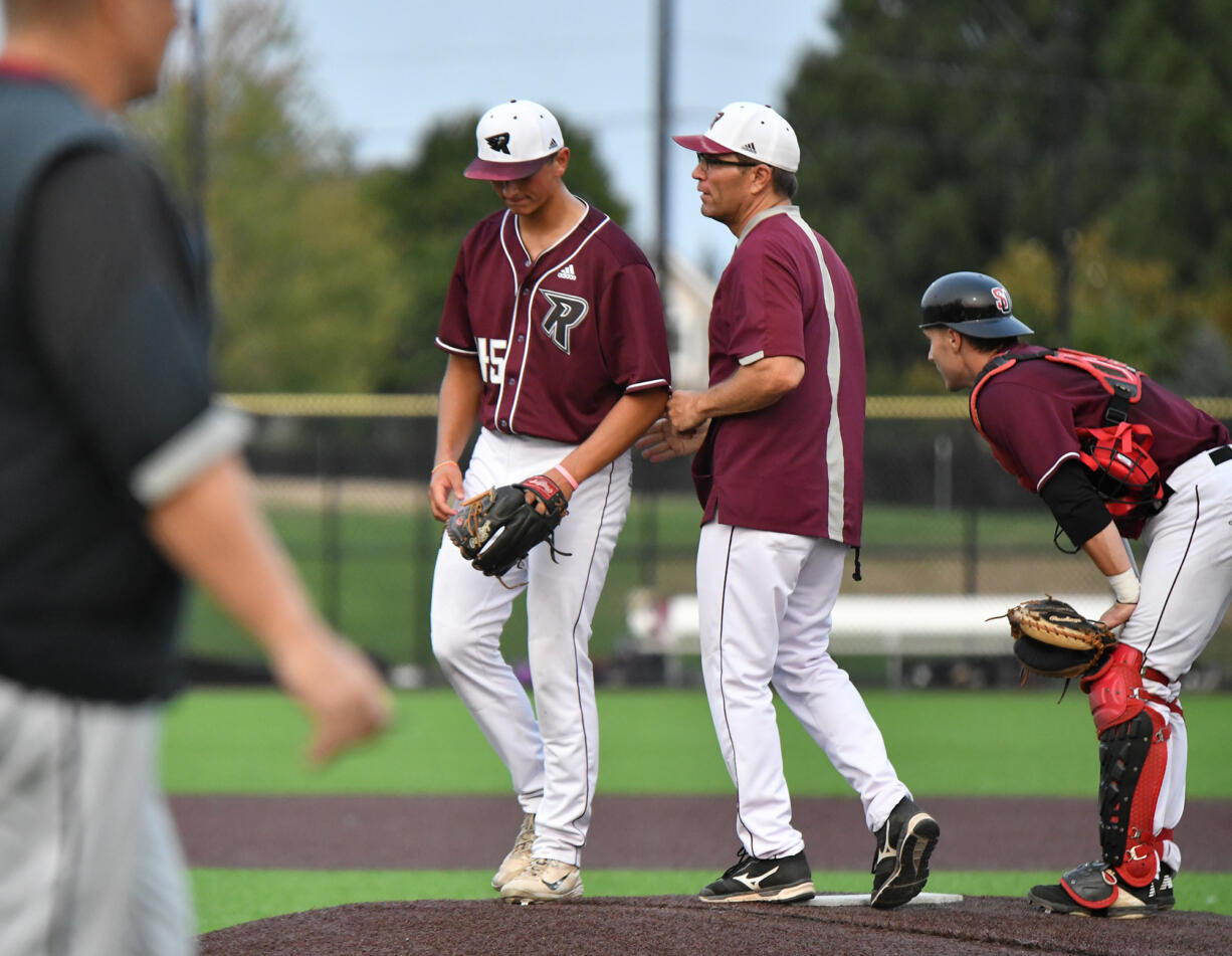 Ridgefield pitcher Brock Gillis, left, walks back to the dugout after getting pulled Saturday, Aug. 14, 2021, during the Raptors' 13-6 loss to Corvallis in a playoff game at the Ridgefield Outdoor Recreation Complex.