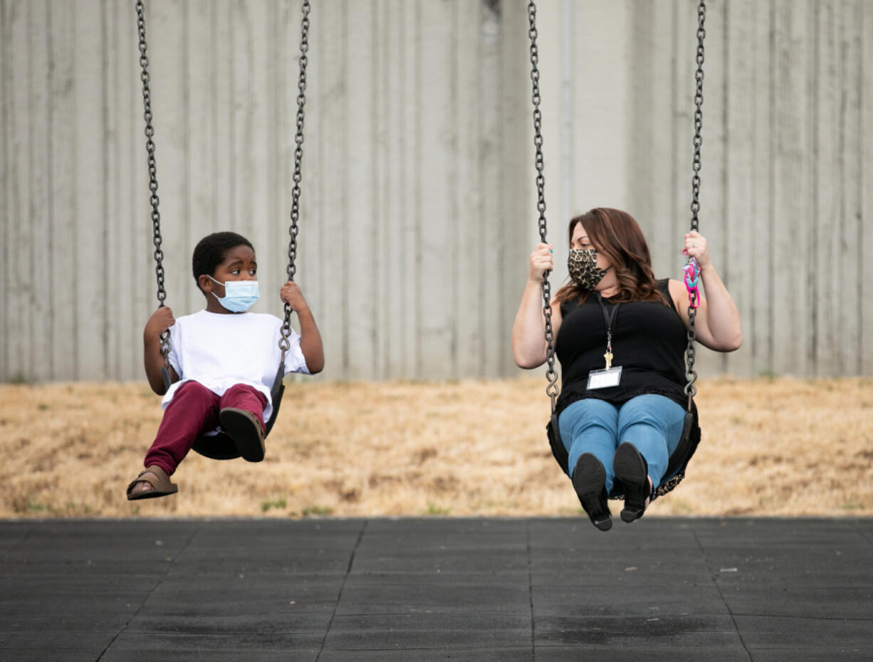 Kindergarten teacher Chelsea Hendryx shows incoming kindergartner Hakeem Hardnett, how to use the swings during recess at Hazel Dell Elementary School as part of Vancouver Public Schools' Jump Start program. Roughly 900 students across the distric attended Jump Start, a two-week program for students to familiarize themselves with rules and routines of school.