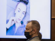 Defendant David Bogdanov listens to the prosecution's opening statement, with a photo of 17-year-old Nikki Kuhnhausen on a projection screen behind him, at his murder trial Tuesday morning in Clark County Superior Court. Bogdanov is accused of strangling the transgender teen.