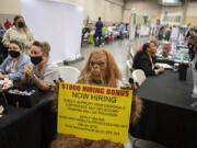 A person dressed as Sasquatch greets those seeking employment at a job fair on Thursday afternoon. The fair drew more than 100 employers looking to meet with job seekers to the Clark County Event Center at the Fairgrounds. At top, Henry Pio of Hazel Dell, from left, talks with Congresswoman Jaime Herrera Beutler as she greets his stepdaughter, Geovanna Alarcon, who is looking for employment.