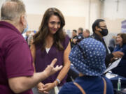 Henry Pio of Hazel Dell, from left, talks with Congresswoman Jaime Herrera Beutler as she greets his stepdaughter, Geovanna Alarcon, who is looking for employment, during a job fair at the Clark County Event Center in August.