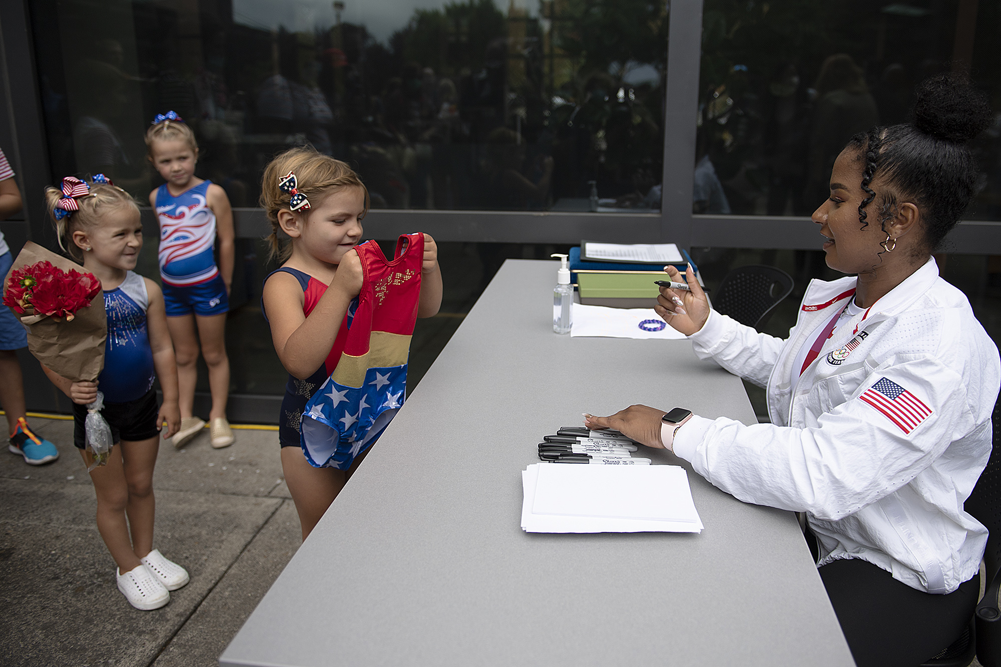 Young gymnasts Hadley Cherry, 3, from left, Quinn Cherry, 5, and Eliora Bertsch, 5, wait in line outside Vancouver City Hall for an autograph from 2020 Olympic Games silver medal winning gymnast Jordan Chiles following the parade in her honor on Sunday afternoon, Aug. 22, 2021.