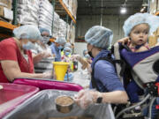 Volunteer Elyce Naray, right, carries her 1-year-old daughter, Elowen, on her back, as she helps package jambalaya meals at the Clark County Food Bank in Vancouver on Saturday. A $15,000 grant from The Church of Jesus Christ of Latter-day Saints to U.S. Hunger covered the cost of the food and packaging materials.