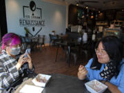 Jennifer Le of Vancouver, left, enjoys a treat at Ice Cream Renaissance in Uptown Village with her sister, Julie, on Monday afternoon. Washington's renewed indoor mask mandate took effect Monday.