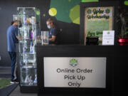 Budtender/cashier Robert Emmons, in blue mask, assists a customer as they pick up an online order inside Main Street Marijuana in Uptown Village on Tuesday morning. The store has put up new signs advising customers that all online orders must now be picked up at indoor counters following a change to state rules three weeks ago.
