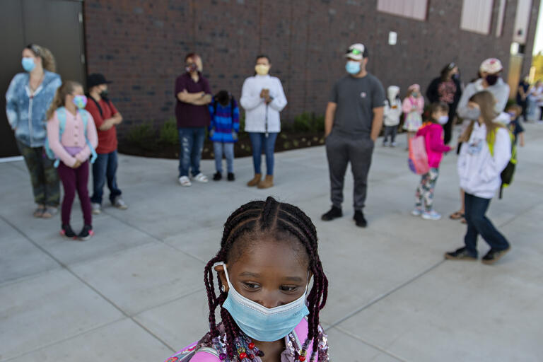 Second-grader Mariama Sandy, 7, front, wears a face mask as she waits outside Marrion Elementary School with fellow students for the first day of class Tuesday morning, Aug. 31, 2021.
