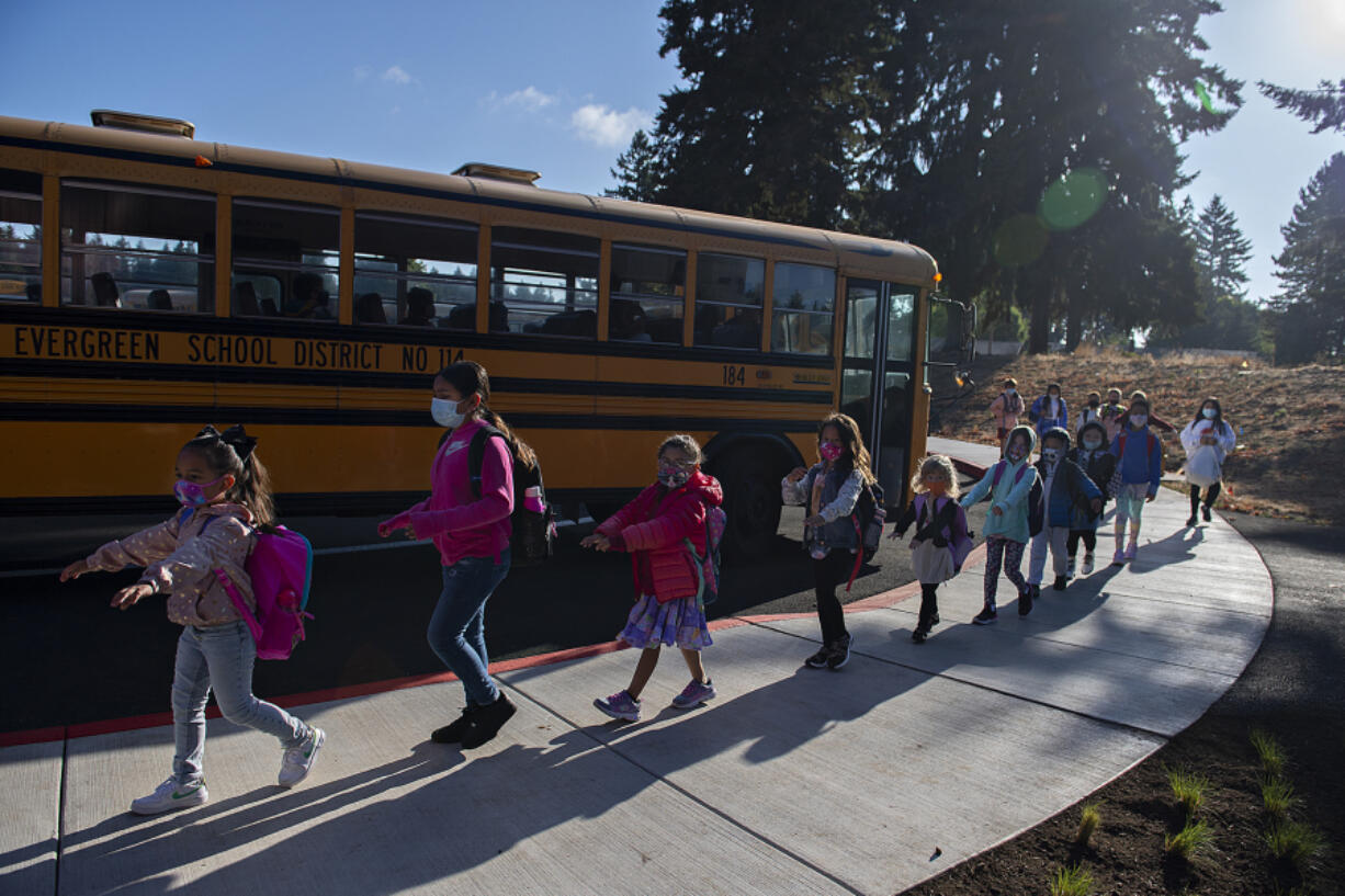 Young students practice social distancing after leaving the school bus for their first day of class at Marrion Elementary School on Tuesday. Thousands of students across multiple Clark County school districts, including Evergreen and Vancouver, began classes for the 2021-22 school year Tuesday amid another year impacted by COVID-19. More districts start Wednesday.