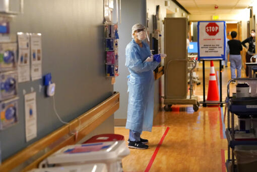 """Registered nurse Diane Miller stands in the """"hot zone,"""" defined by red tape on the floor, as she waits to exchange equipment with a colleague who will remain on the other side of the tape in the COVID acute care unit at UW Medical Center-Montlake, Tuesday, Jan. 26, 2021, in Seattle. King County, where the hospital is located, has been on a downward trend of COVID-19 cases after two-and-a-half straight months of increases. But the current lull could be, and some experts believe will be, upended as more contagious variants of the virus spread throughout United States."""