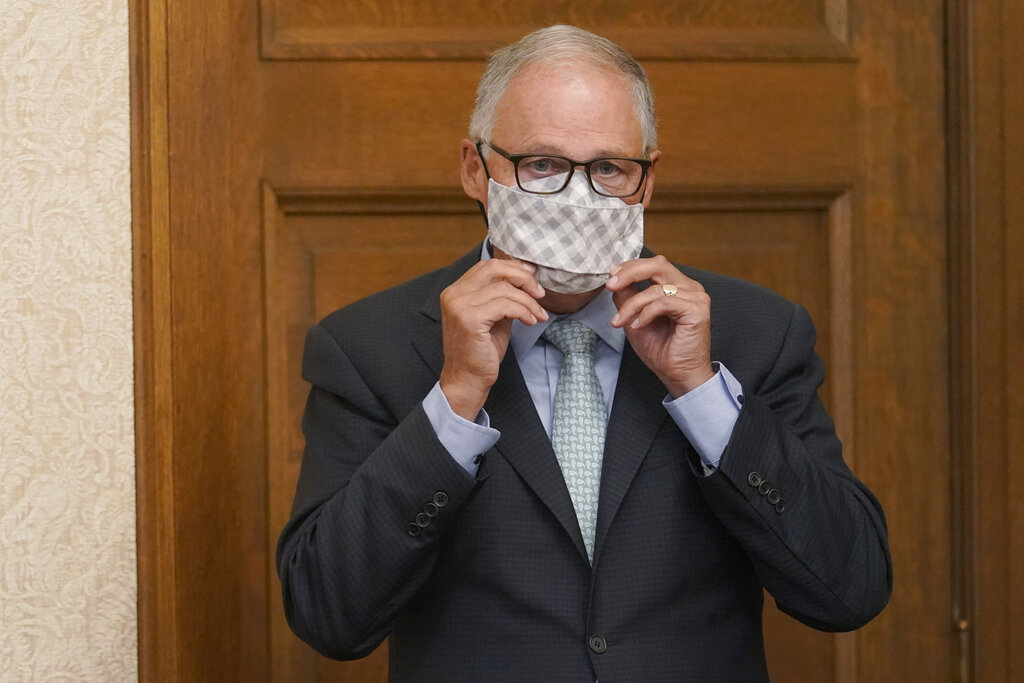Washington Gov. Jay Inslee puts on a mask after speaking at a news conference, Wednesday, Aug. 18, 2021, at the Capitol in Olympia, Wash. Inslee announced that Washington state is expanding its vaccine mandate to include all public, charter and private school teachers and staff, as well as those working at the state's colleges and universities. The governor also expanded the statewide indoor mask mandate in place for non-vaccinated individuals to include those who are vaccinated. (AP Photo/Ted S.