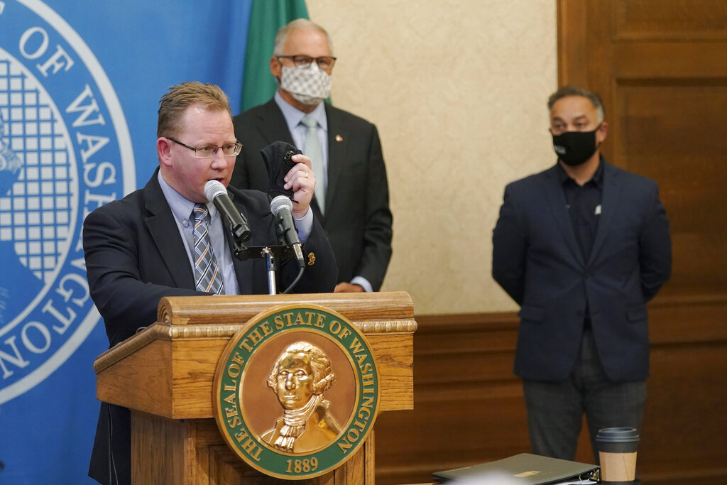 Washington State Superintendent of Public Instruction Chris Reykdal, left, holds up a face mask as he speaks at a news conference, along with Gov. Jay Inslee, center, and Secretary of Health Umair A. Shah, right, at the Capitol, Wednesday, Aug. 18, 2021, in Olympia, Wash. Inslee announced that Washington state is expanding its vaccine mandate to include all public, charter and private school teachers and staff, as well as those working at the state's colleges and universities. The Governor also expanded the statewide indoor mask mandate in place for non-vaccinated individuals to include those who are vaccinated. (AP Photo/Ted S.