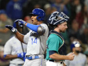 Kansas City Royals' Edward Olivares (14) celebrates his two-run home run as Seattle Mariners catcher Tom Murphy looks away in the 12th inning of a baseball game Friday, Aug. 27, 2021, in Seattle.