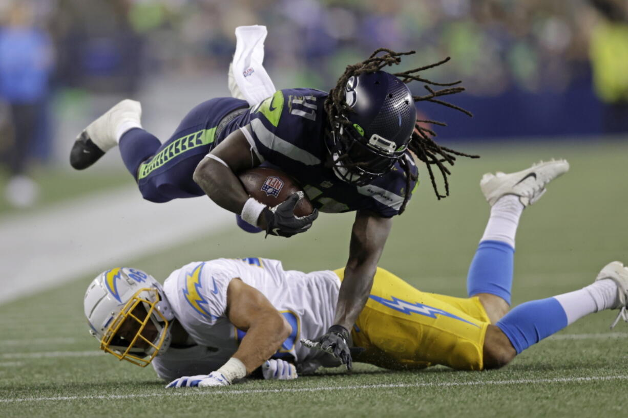 Seattle Seahawks running back Alex Collins dives over Los Angeles Chargers safety Ben DeLuca as he carries the ball during the second half of an NFL football preseason game, Saturday, Aug. 28, 2021, in Seattle.