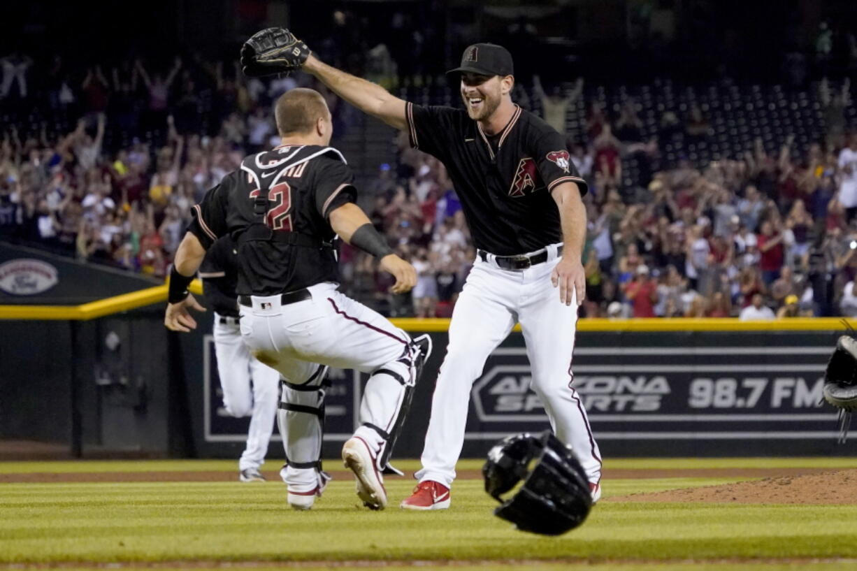 Arizona Diamondbacks starting pitcher Tyler Gilbert, right, celebrates after his complete game no hitter against the San Diego Padres with catcher Daulton Varsho, Saturday, Aug. 14, 2021, in Phoenix. It was Gilbert's first career start. The Diamondbacks won 7-0.