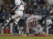 Houston Astros' Kyle Tucker (30) slides home to score on during the eighth inning Monday in Seattle. (Ted S.