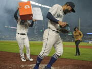 Seattle Mariners' Abraham Toro, center, has a cooler of water dumped on him by teammate Luis Torrens, left, as Toro takes part in an interview after the team's baseball game against the Houston Astros, Tuesday, Aug. 31, 2021, in Seattle. Toro hit a grand slam in the eighth inning to give the Mariners a 4-0 win. (AP Photo/Ted S.