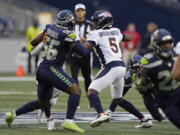 Denver Broncos quarterback Teddy Bridgewater (5) looks for a receiver while under pressure from Seattle Seahawks linebacker Jordyn Brooks (56) during the first half of an NFL preseason football game Saturday, Aug. 21, 2021, in Seattle.