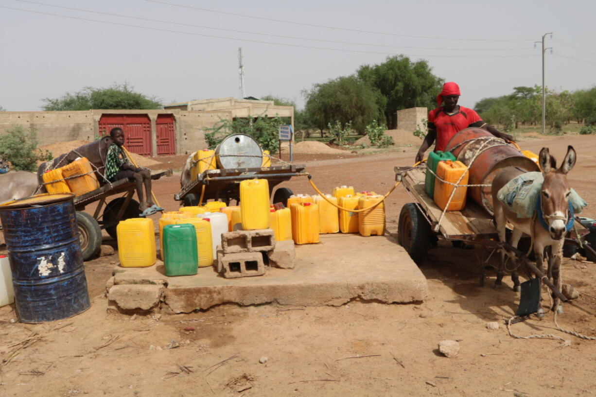 Residents fill up water containers in Dori, Burkina Faso, Wednesday July 7, 2021. Violence by fighters linked to al-Qaida and the Islamic State in Burkina Faso is on the rise, and with it, so is the recruitment of child soldiers, according to reports.