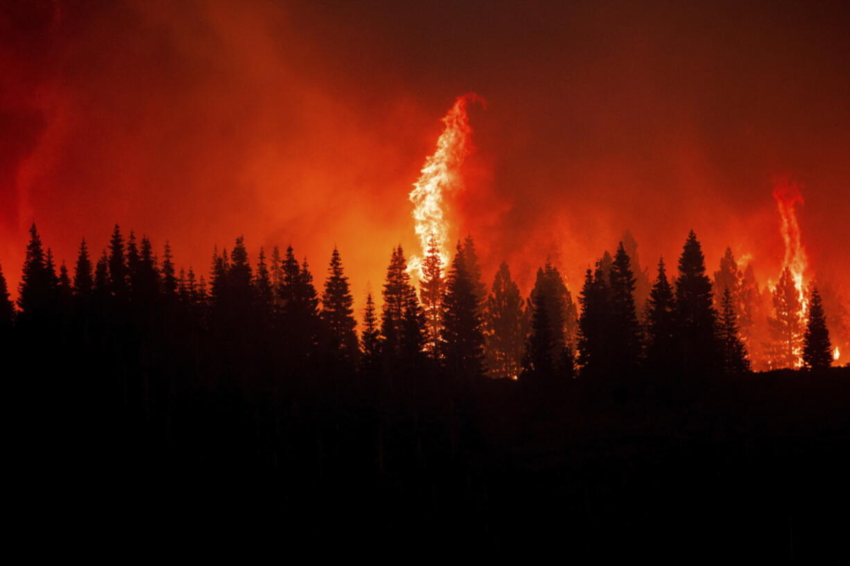 Flames from the Dixie Fire crest a hill in Lassen National Forest, Calif., near Jonesville on Monday, July 26, 2021.