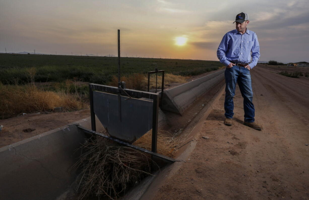 Will Thelander, a partner in his family's farming business, looks into a dry irrigation canal on his property, Thursday, July 22, 2021, in Casa Grande, Ariz. The Colorado River has been a go-to source of water for cities, tribes and farmers in the U.S. West for decades. But climate change, drought and increased demand are taking a toll. The U.S. Bureau of Reclamation is expected to declare the first-ever mandatory cuts from the river for 2022.