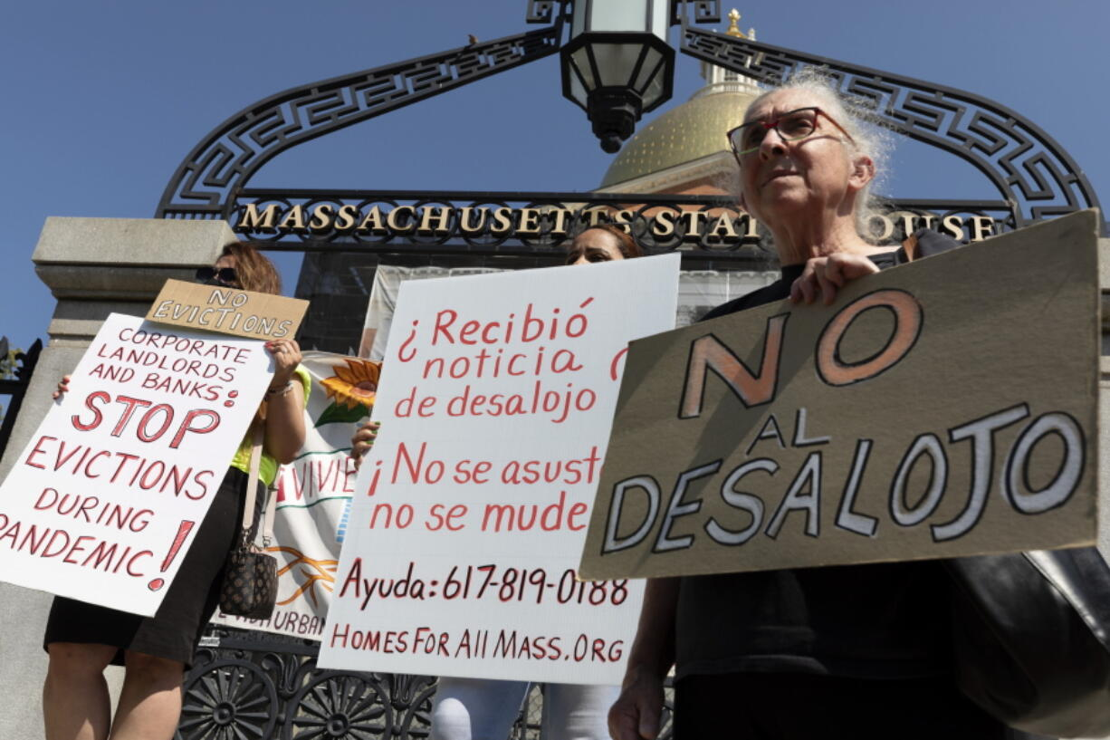 People from a coalition of housing justice groups hold signs protesting evictions during a news conference outside the Statehouse, Friday, July 30, 2021, in Boston.