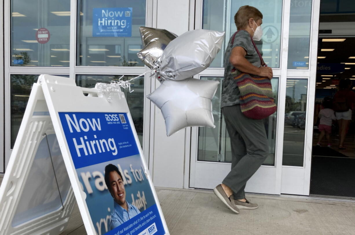 A shopper passes a hiring sign while entering a retail store in Morton Grove, Ill., Wednesday, July 21, 2021. Despite an uptick in COVID-19 cases and a shortage of available workers, the U.S. economy likely enjoyed a burst of job growth last month as it bounces back with surprising vigor from last year's coronavirus shutdown. The Labor Department's July jobs report Friday, Aug. 6 is expected to show that the United States added more than 860,000 jobs in July, topping June's 850,000, according to a survey of economists by the data firm FactSet.   (AP Photo/Nam Y.
