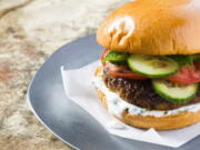 This image released by Milk Street shows a recipe for Indian-spiced pork burgers. The garam masala, cayenne and cumin first are mixed into a paste made from tangy yogurt, egg yolk and breadcrumbs, which helps the burgers stay moist. Mixing the spiced paste into the meat ensures the flavor is distributed evenly throughout each burger.