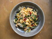 This image released by Milk Street shows a recipe for orecchiette with sausage and arugula.