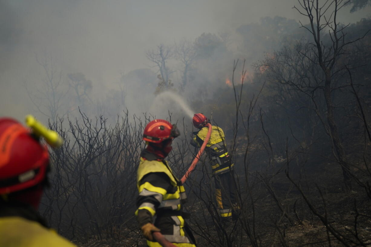Firemen use a hose to extinguish a fire in a forest near Le Luc, southern France, Tuesday, Aug. 17, 2021.