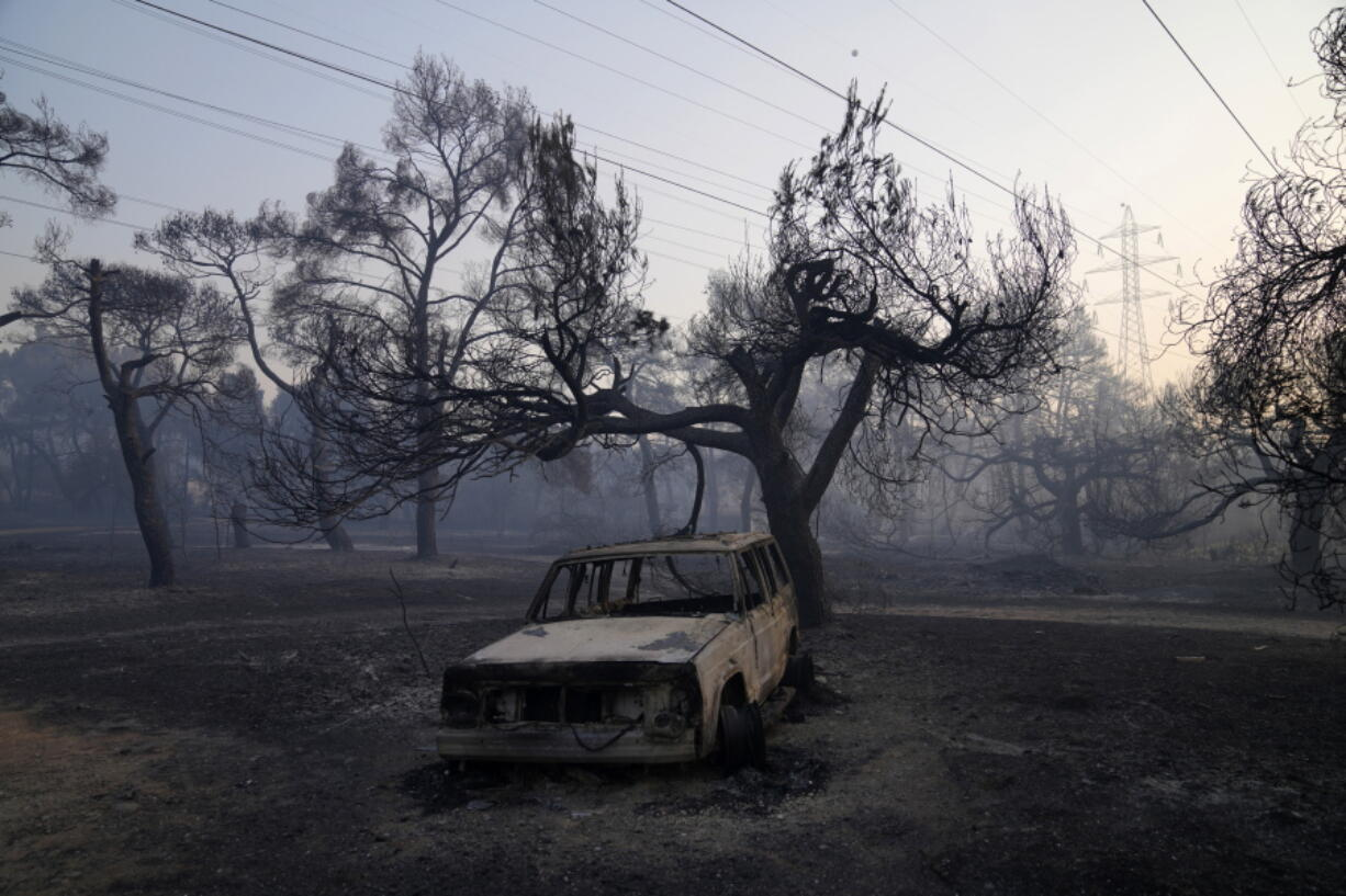 A burned car is seen after a wildfire in Varibobi area, northern Athens, Greece, Wednesday, Aug. 4, 2021. More than 500 firefighters struggled through the night to contain a large forest blaze on the outskirts of Athens, which raced into residential areas Tuesday, forcing thousands to flee. It was the worst of 81 wildfires that broke out in Greece over the past 24 hours, amid one of the country's most intense heatwaves in decades.