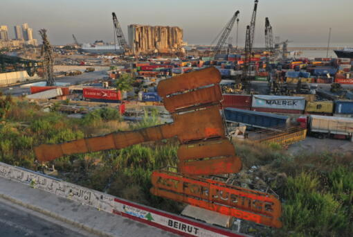 A justice symbol monument is seen in front of towering grain silos that were gutted in the massive August 2020 explosion at the port that claimed the lives of more than 200 people, in Beirut, Lebanon, Wednesday, Aug. 4, 2021. A year after the deadly blast, families of the victims are consumed with winning justice for their loved ones and punishing Lebanon's political elite, blamed for causing the disaster through their corruption and neglect.