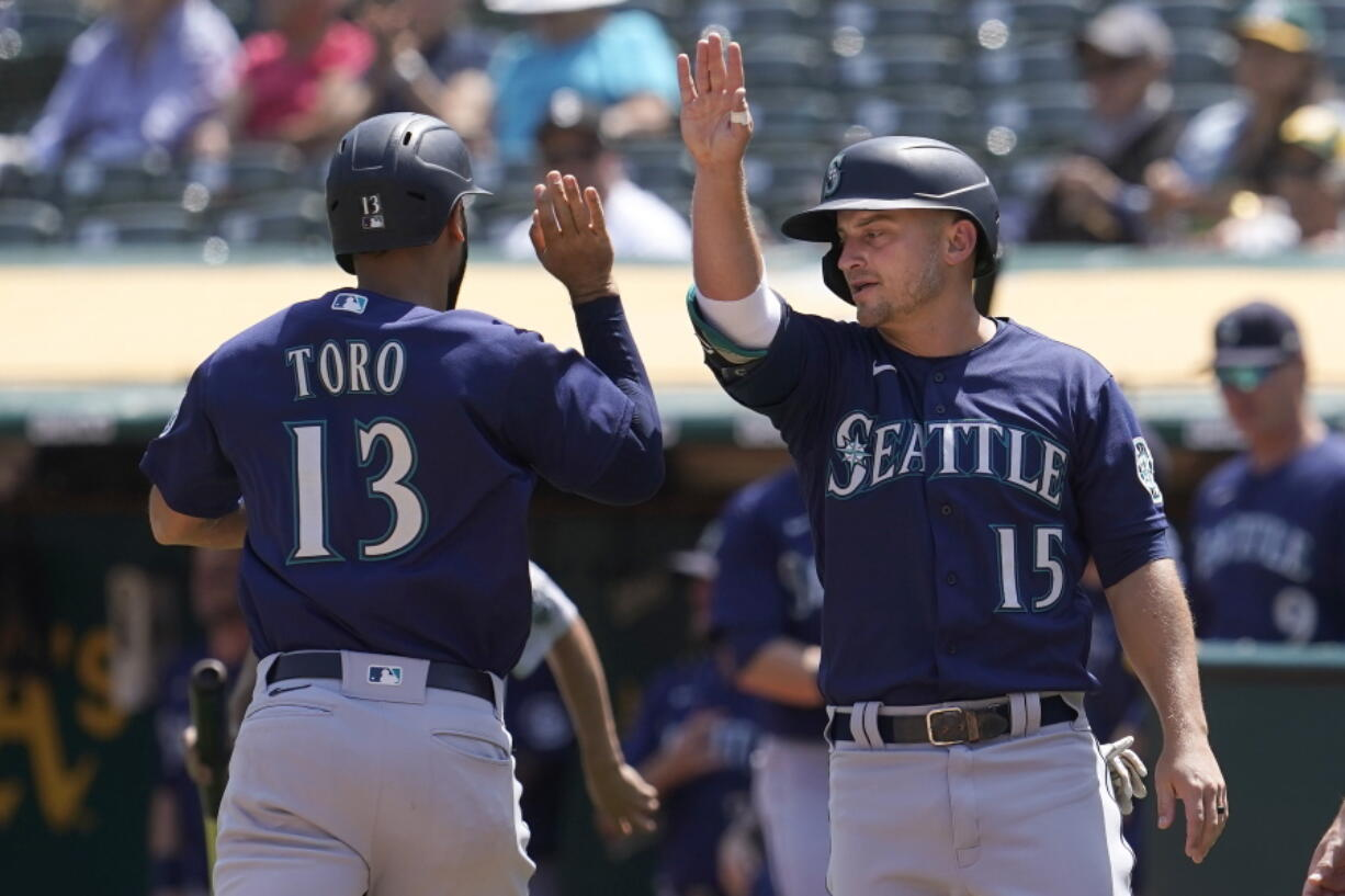 Seattle Mariners' Abraham Toro, left, celebrates with Kyle Seager after both scored on a two-run single by Luis Torrens during the third inning of a baseball game against the Oakland Athletics in Oakland, Calif., Tuesday, Aug. 24, 2021.