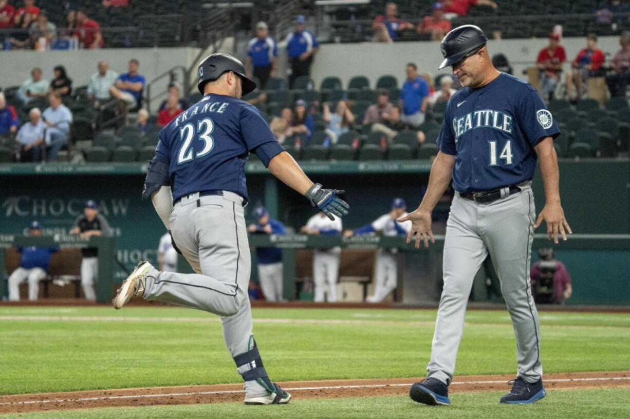 Seattle Mariners' Ty France (23) is congratulated by third base coach Manny Acta (14) after hitting a two-run home run off Texas Rangers relief pitcher Joe Barlow during the 11th inning of a baseball game Thursday, Aug. 19, 2021, in Arlington, Texas. Seattle won 9-8.